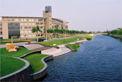 """""""问源""""滨水广场位于上海同济大学校园中部,紧邻图书馆、教学楼南楼和饮食中心,宽10米校园水系由西侧流过。同济大学吴人韦教授设计并主持现场施工。广场于2001年9月建成,占地仅3亩,可谓方寸之地。但""""问源""""广场所体现的设计匠心与造园艺术手法却耐人寻味。 广场主要由滨水休憩台地和缓坡草坪构成。草坪的地面高度由165厘米这一人性化尺度逐步向外降低至30厘米左右这一适宜坐憩的地面高度。这种处理手法在功能上使内部休憩空间得以闹中取静,同时尺度上又不失亲和性。由于竖向"""