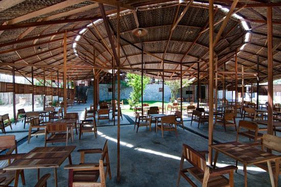 Salvaged Ring是位于越南芽庄乡村公路旁的一个咖啡屋。业主是当地的一个木匠,多年的工作积累了大量的边角料。他希望为这些废材赋予新的生命,以免被白白丢弃遗忘。在这个想法的支撑下该项目应运而生。 咖啡屋由越南知名工作室a21 studio设计,给人的第一眼印象便是从公路向下延伸到河岸的不寻常弧状茅草屋顶。屋顶将两种不同的高度巧妙地合为一体,柔化了下方的制成结构。一条具有异国情调的小道将客人从室外引进由环形屋顶勾勒出的内部庭院。  越南SALVAGED RING咖啡厅(一) 众所周知,庭院是越南地区文