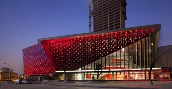 """建筑设计: 方正实用的平面布局,使二维上的""""纯平外轮廓""""与""""纯平墙身""""最大程度保证了室内使用空间的完整高效,也生动的展现了人们心目中对称、端庄、典雅、具有韵律的双塔形象。 三层通高的剧场大厅,由高耸的折面型玻璃幕墙围合,其形态犹如竖琴琴弦,优雅笔挺,海风轻抚,仿佛就能拨动琴弦。 观演大厅的观众席,象海浪涌起后形成的漩涡,池座,楼座,层层叠叠地把镜框式舞台环绕其中。"""