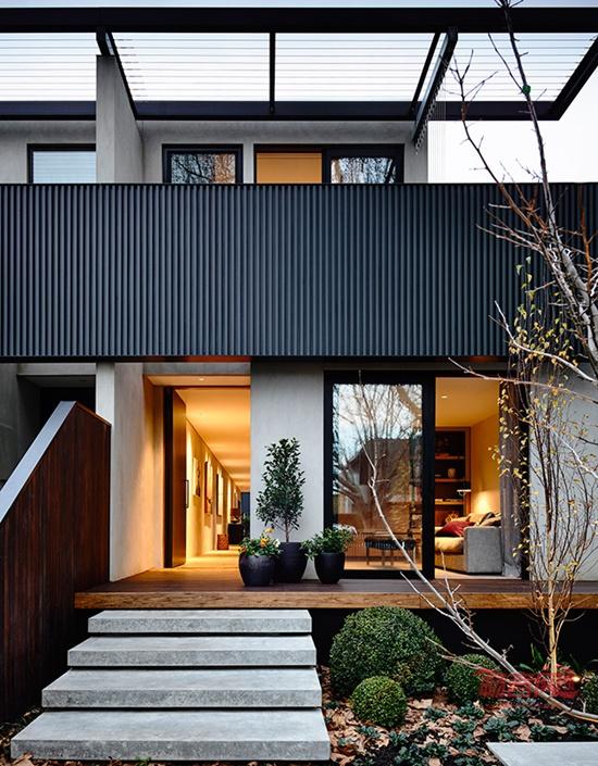 建筑设计公司InForm完成了澳大利亚埃尔伍德的一栋联排别墅设计。 一道混凝土界墙纵向贯穿了别墅,将其与相邻的两个单元(一排有三个单元)分隔开来,同时也从视觉上连通了房前的入口处与房后的花园。 在别墅一层中央,是一个玻璃围墙的天井,围绕天井布局了书房、厨房和客厅,天井旁边有一个手工制成的木质楼梯。 楼上有两间豪华卧室和一间瑜伽室。前面卧室的外墙上悬挂着黑色木质栏杆,位于门廊上方,另外两个单元也是如此,这样就形成了整栋联排别墅的统一元素之一。