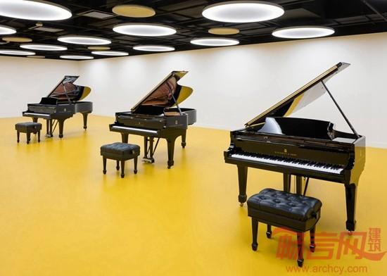 建筑师Annabelle Selldorf 完成了钢琴制造商斯坦威(Steinway & Sons)位于纽约的钢琴展示大厅。方案中大量采用了木质设计元素,与斯坦威手工钢琴的特点是相呼应。  这座分为上下两层展示大厅位于曼哈顿中心一栋高楼的底层,总面积为1765平方米,其中包括一个零售区、一个74座的演奏厅、一个排练区和一间录音室。  大厅前部采用了玻璃墙,人们从外面可以清楚地看到零售区,这里采用了橡木地板和曲形木片制成的独特天花板。