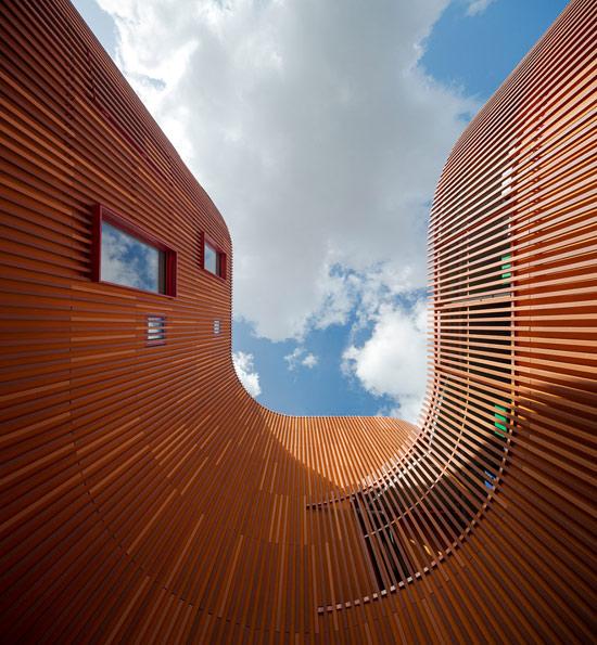 丹麦建筑事务所COBE最新的幼儿园作品在哥本哈根完工。这座幼儿园有突出的弧形曲线墙与葱郁的屋顶花园。建筑外表皮特殊的材料,其形式与色彩与周围的建筑有相当的呼应,同时在色彩名都上保持了幼儿园建筑的特色。  COBE的创始人Dan Stubbergaard提到他们希望通过这个项目创造出世界级水平的幼儿日间护理中心,让孩子在最佳的环境中学习,创造,成长。幼儿园所在地区是哥本哈根老人院和老年社区集中的地方,因此设计也竭力让幼儿园与周围环境保持协调。很多人选择在这里度过自己的晚年,导致的结果是这些人的儿孙辈们也在