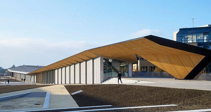 """隈研吾完成了瑞士洛桑EPFL校园建筑。这一名为""""屋顶下""""的项目,名称揭示了其拥有的巨大坡屋面。这一屋面伸出了235米,为下方三层艺术科学馆、科技问询厅和咖啡馆空间提供超大天棚。这一艺术俱乐部建筑将成为瑞士洛桑联邦理工学院的最新项目,已有建筑包括SANAA设计的劳力士学习中心。隈研吾的方案遵循了地势坡度,其中每个方体容纳不同功能区。"""